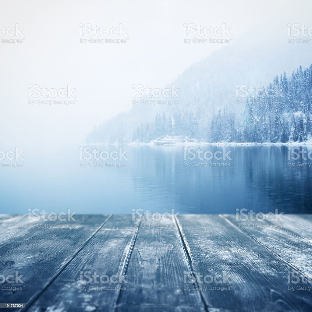 Winter background. Wooden floor and defocused winter landscape on background stock photo