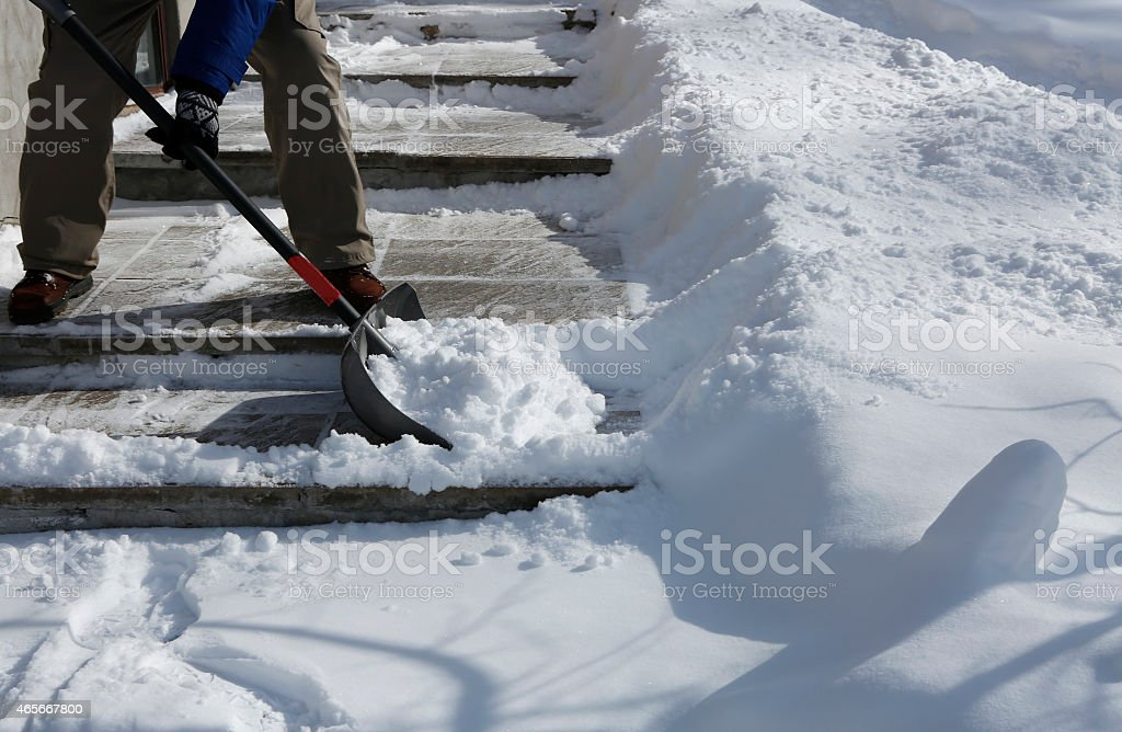Winter blizzard: Cleaning the stairway stock photo