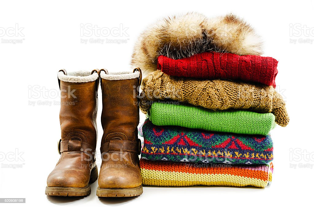 Winter boots, cap and stack of various sweaters. Winter style stock photo
