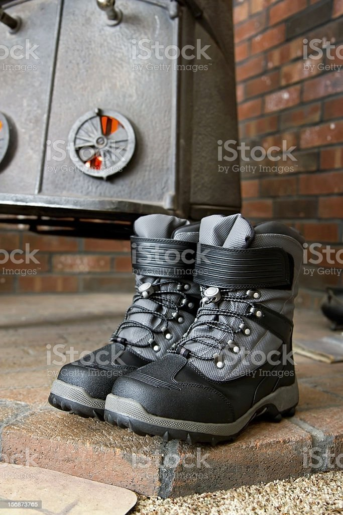 Winter Boots drying in front of a Wood Stove royalty-free stock photo