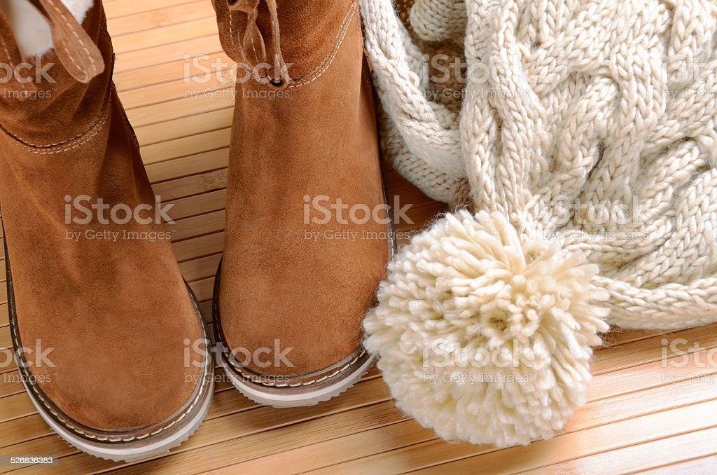 winter boots, hat and scarf on the floor stock photo