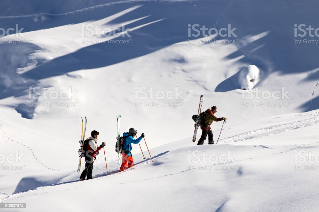 Winter Breaks - Group of friends walking up in the back country mountain stock photo