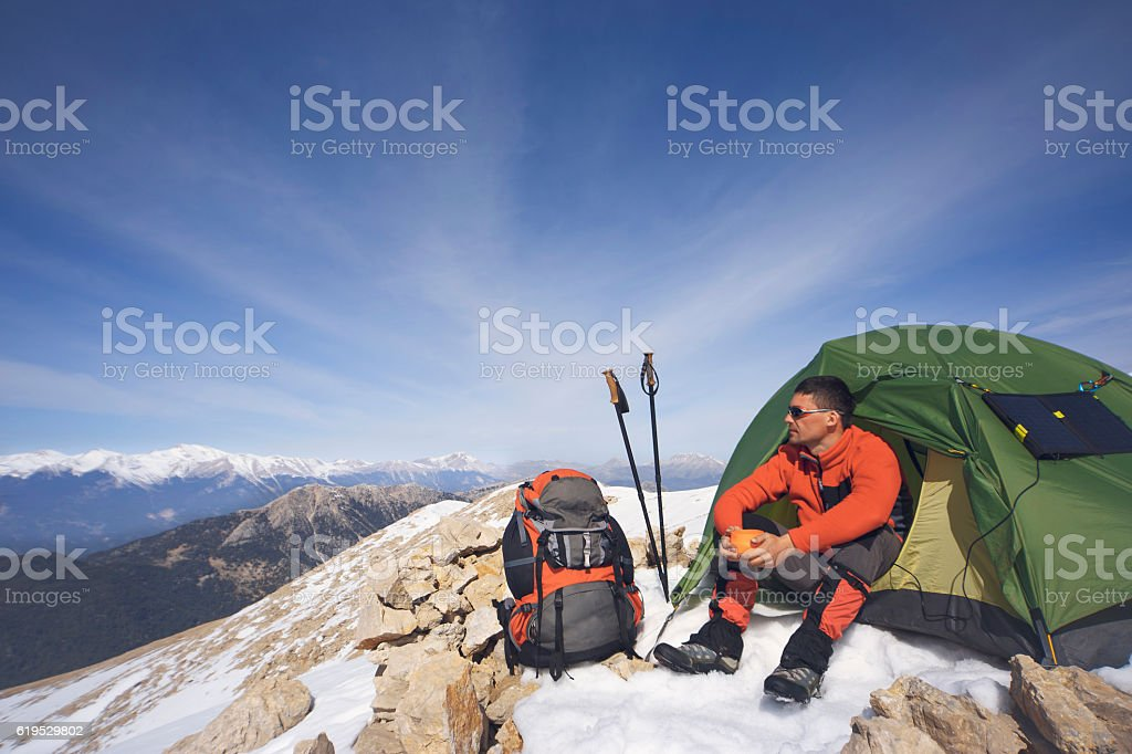 Winter camping in the mountains with a backpack and tent. stock photo