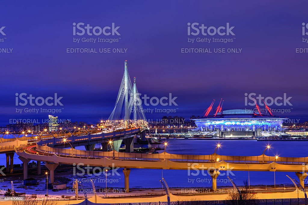 Winter cityscape with stadium, cable-stayed bridge and highway at night. stock photo