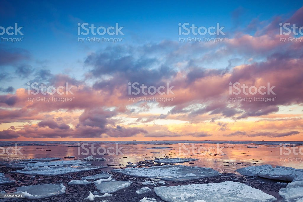 Winter coastal landscape with floating ice on sea and clouds stock photo