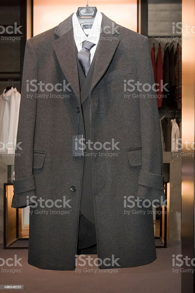 Winter coat, suit, shirt and necktie on a hanger. stock photo