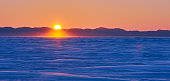 Winter color sunset frozen snow winter sea, remote people fishermen