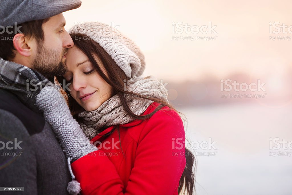 Winter couple hugging stock photo
