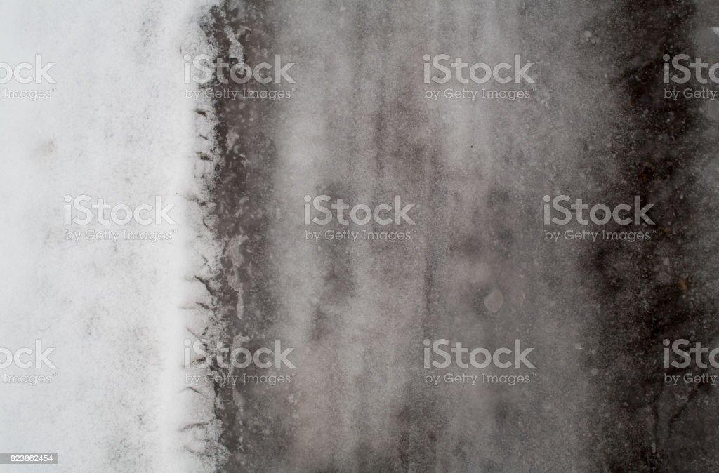 Winter dark melted snow background stock photo