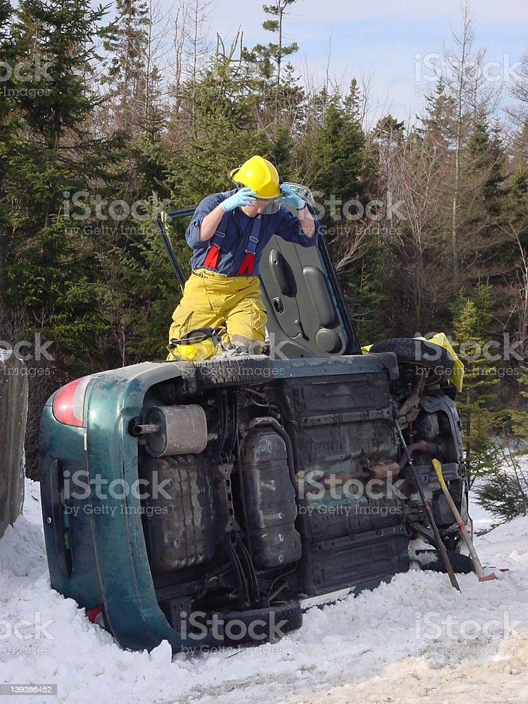 Winter driving auto accident, with fireman on top royalty-free stock photo