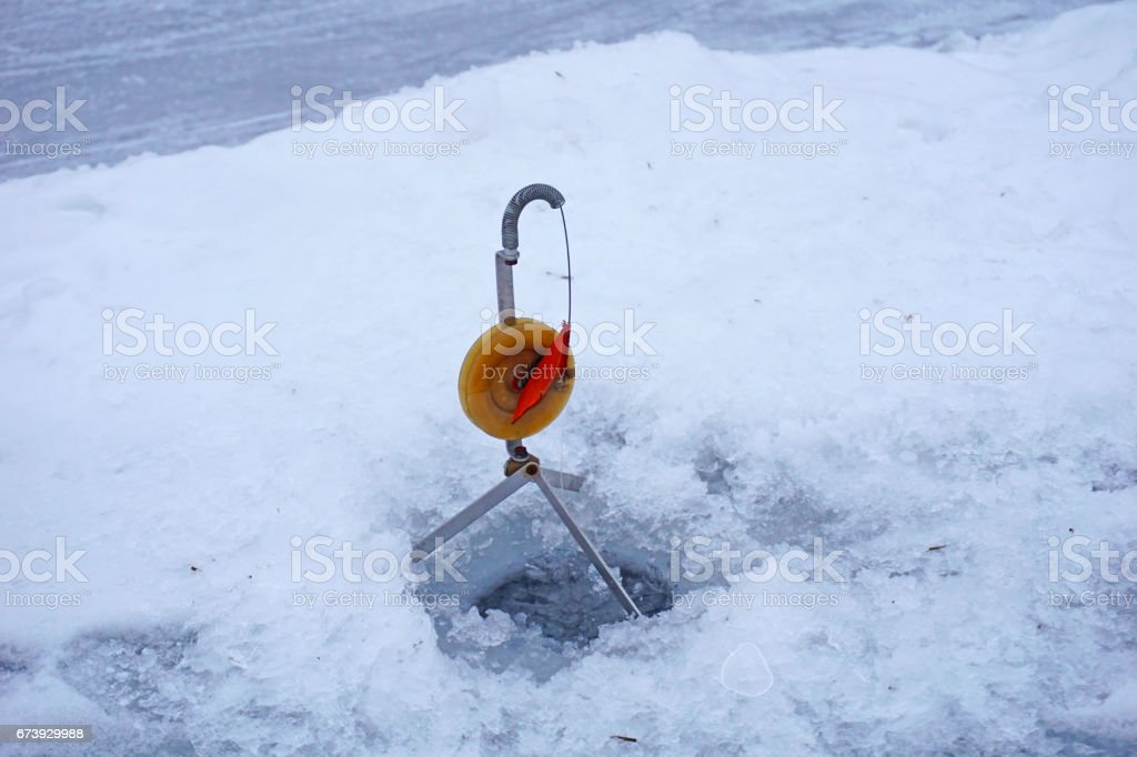 Winter fishing in the hole in the icy lake stock photo
