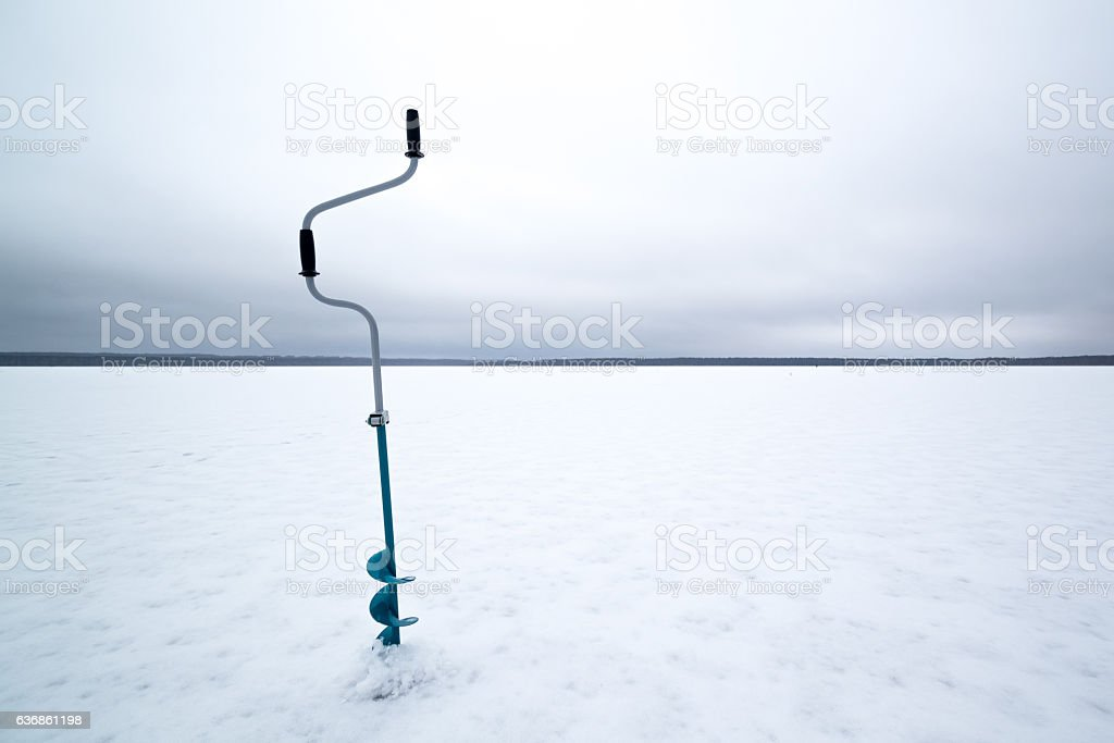 Winter fishing on ice in the middle of a frozen stock photo