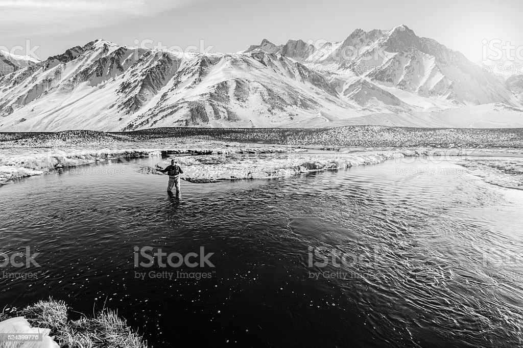 Winter Fly Fisherman With Big Mountain Behind stock photo