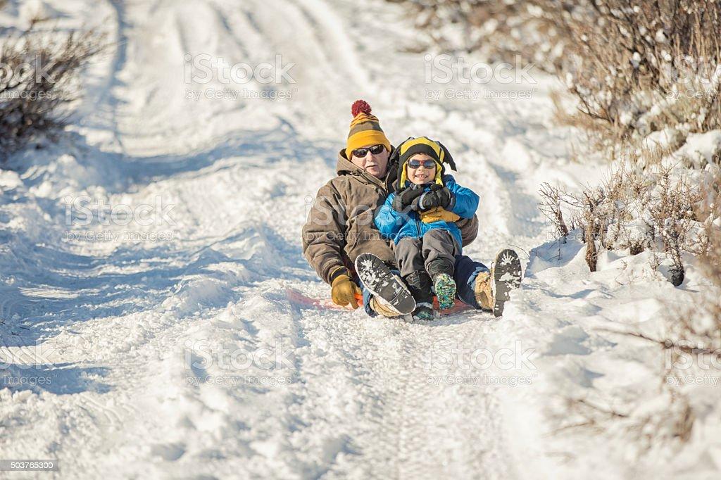 Winter Fun: Grandfather and Grandson Sledding stock photo