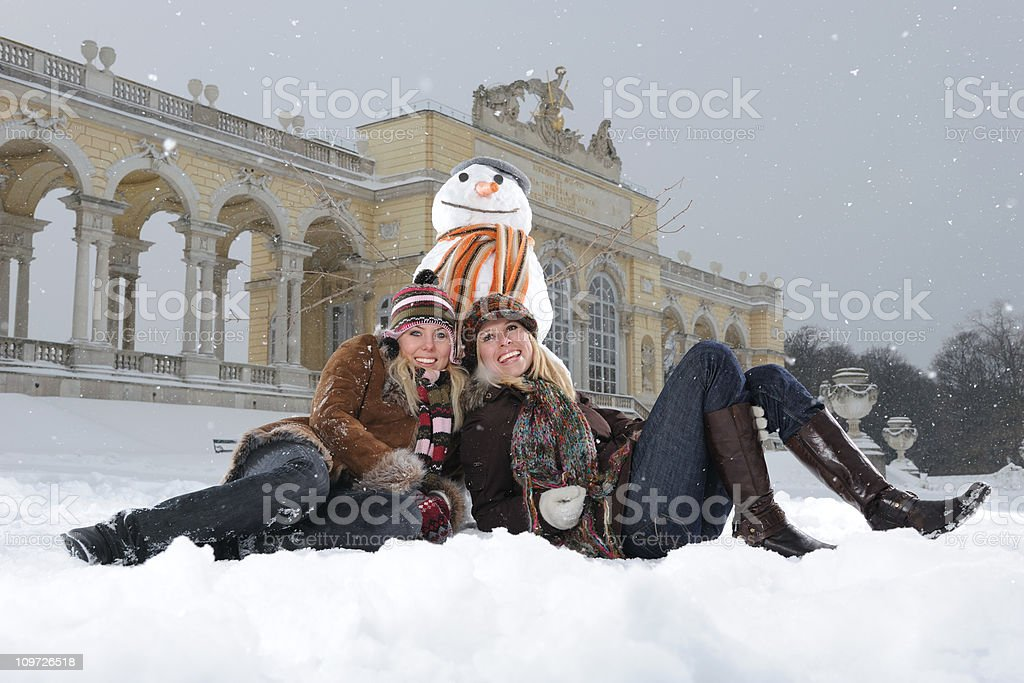 Winter Fun - Two beautiful smiling Women with Snowman royalty-free stock photo