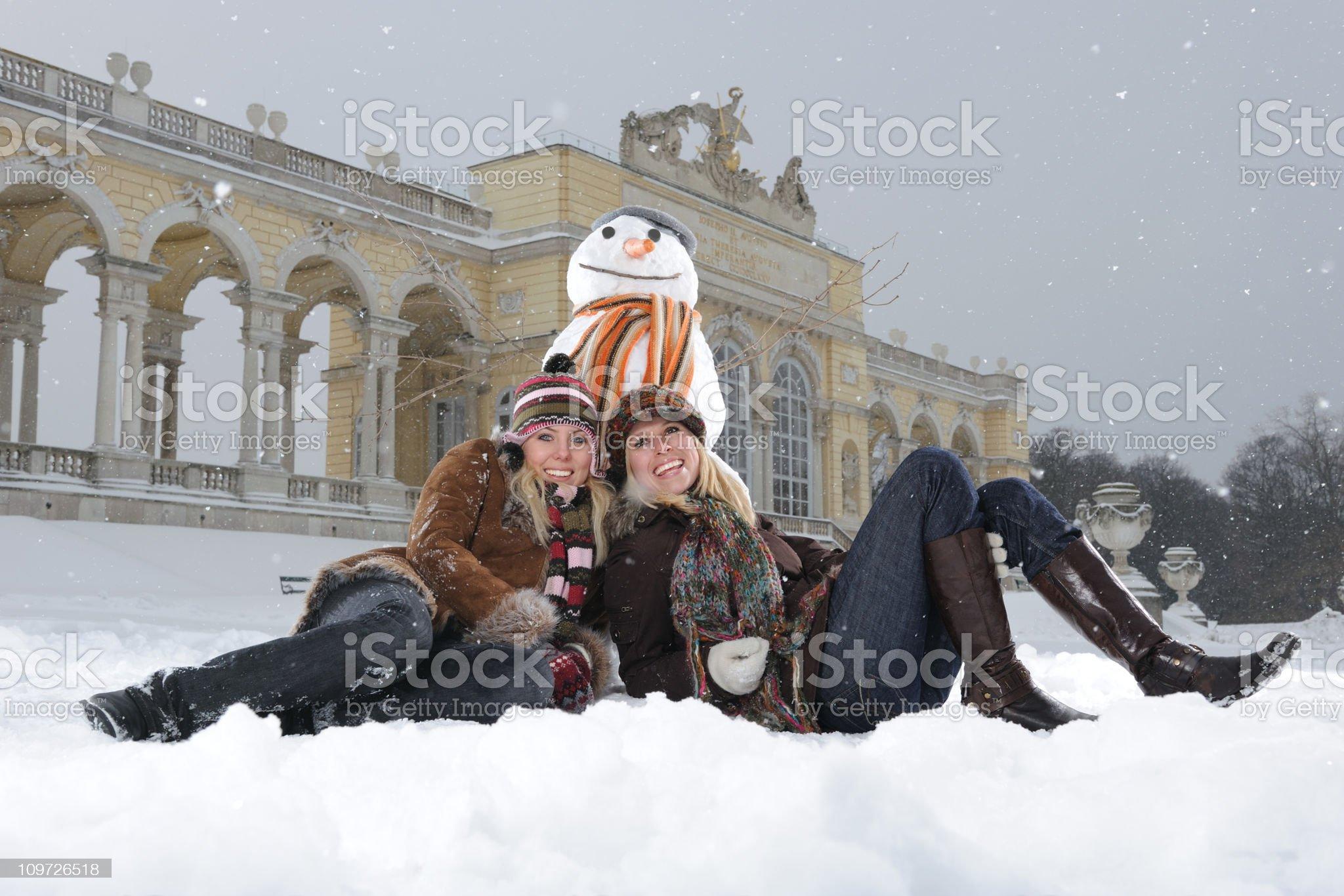 Winter Fun - Two beautiful smiling Women with Snowman royalty-free stock photo