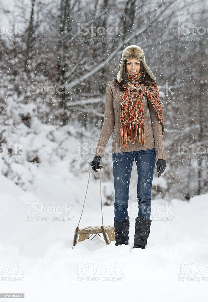 Winter Fun, Woman pulling a Wooden Sled, Copy Space royalty-free stock photo
