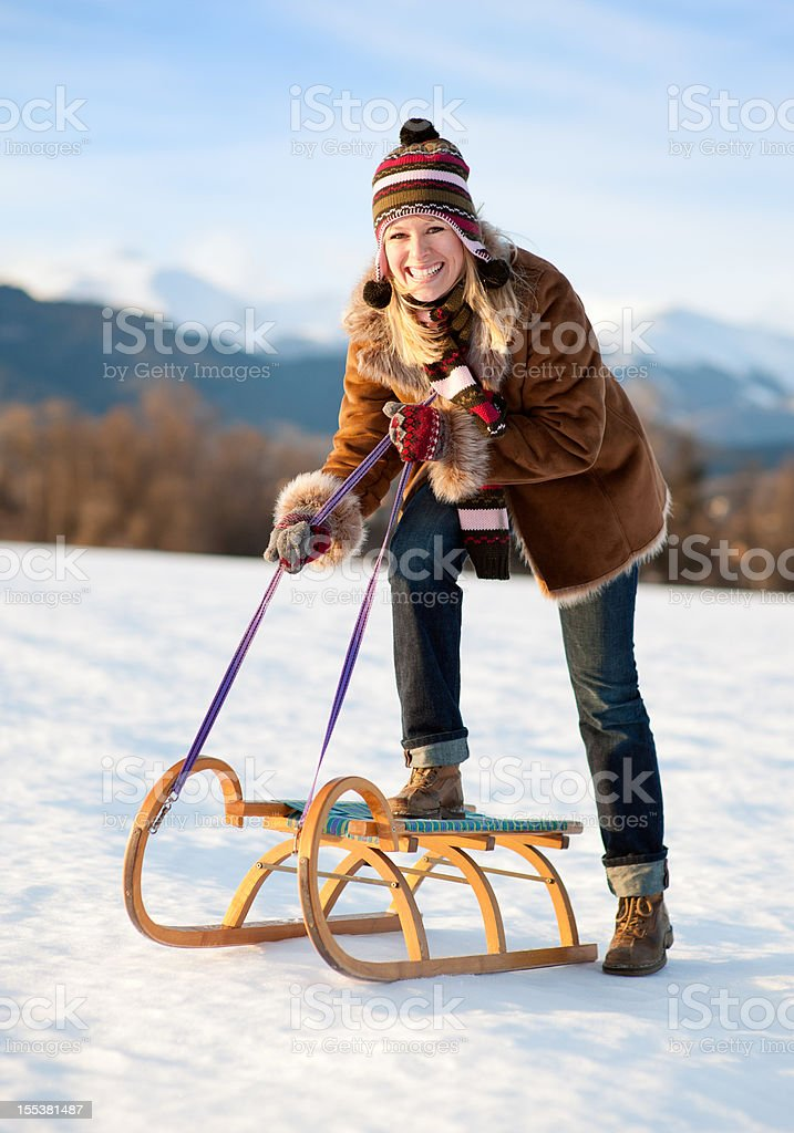 Winter Fun - Woman riding on a Wooden Sled (XXL) royalty-free stock photo