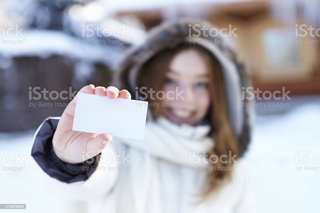 Winter. Girl with blank visiting card.
