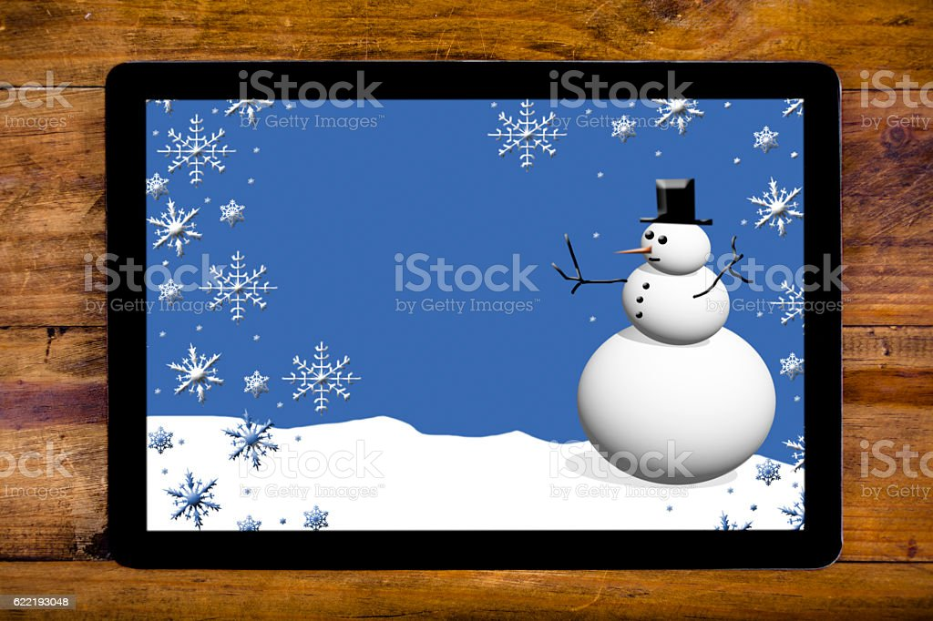 Winter greeting card snowman scene on digital tablet. stock photo