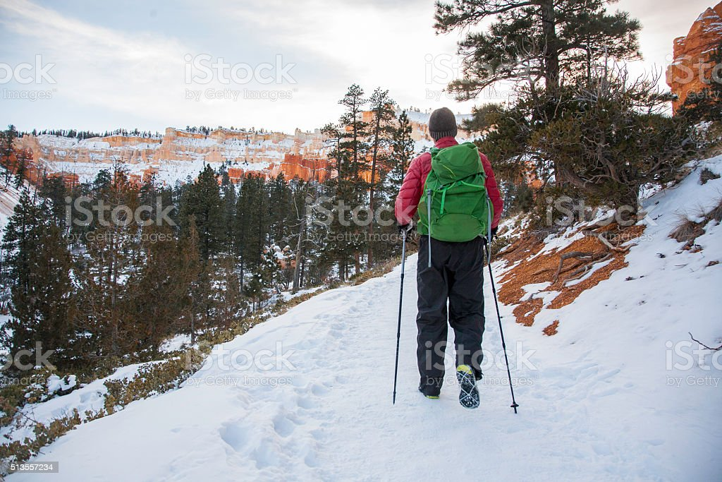 Winter Hiker walking with crampons on snowy mountain landscape stock photo
