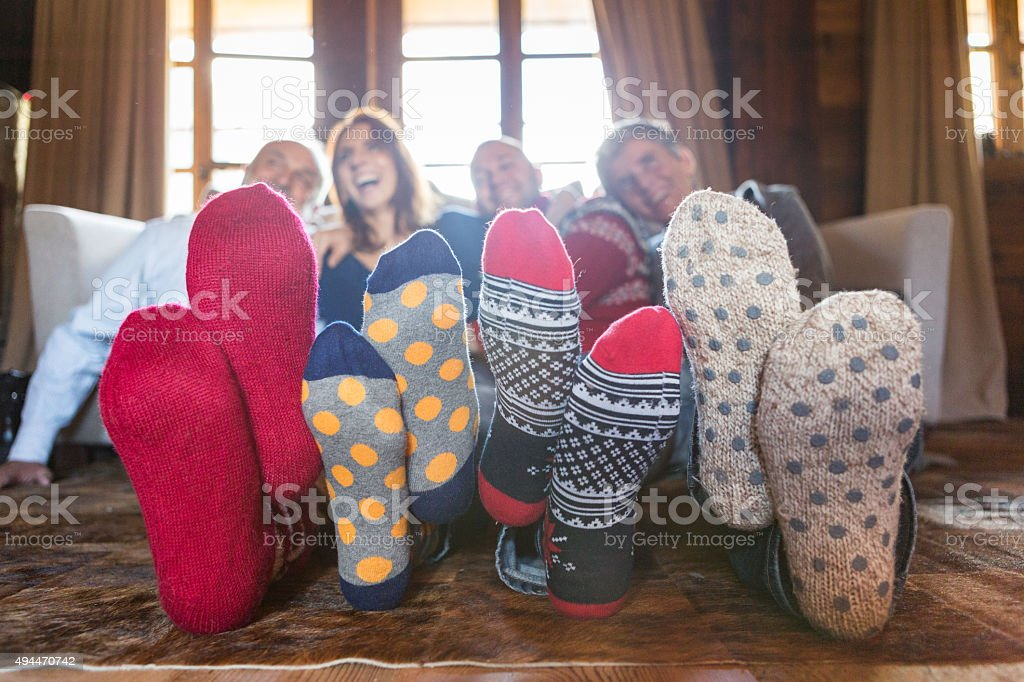 Winter home: family on living room carpet with wool socks stock photo