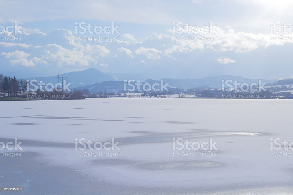 Winter landscape and frozen lake in the foreground stock photo