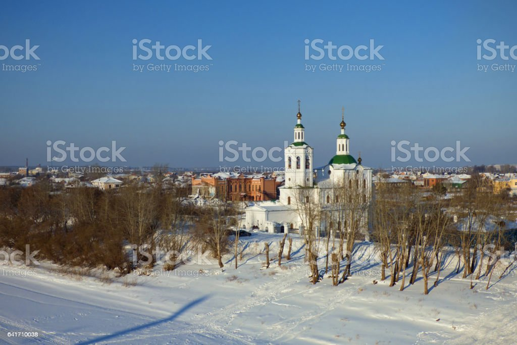 Winter landscape. Church on the bank of frozen river stock photo