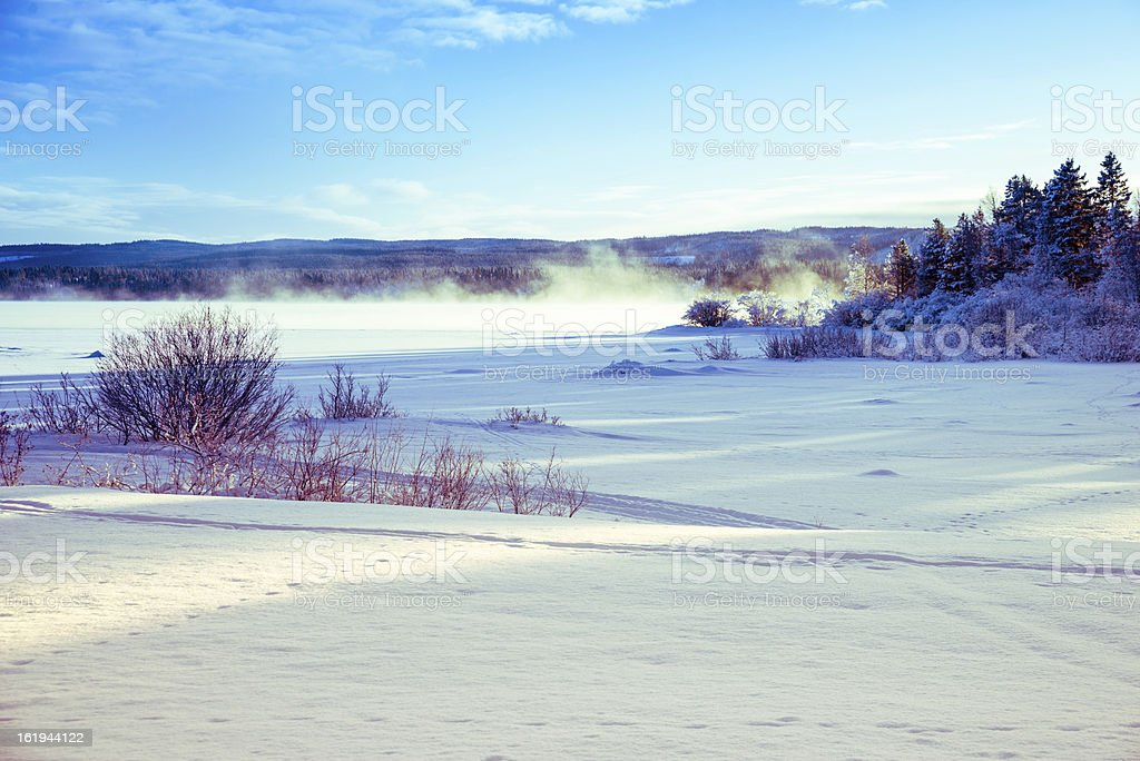 winter landscape of icy and snowy lake with fog royalty-free stock photo