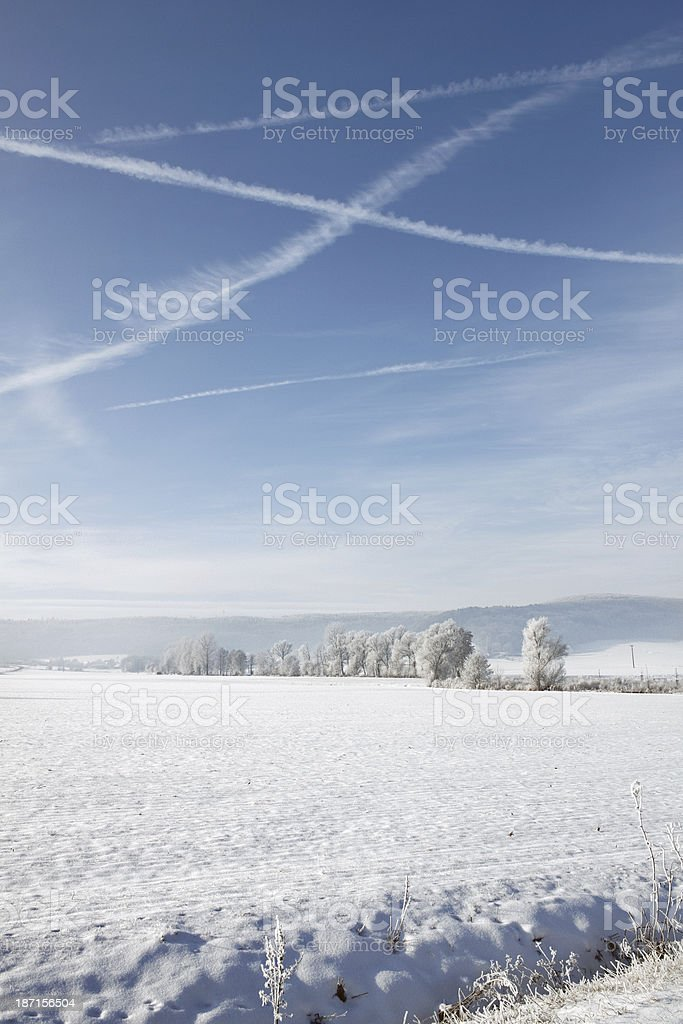 Winter landscape with crossed vapour trails in the blue sky royalty-free stock photo
