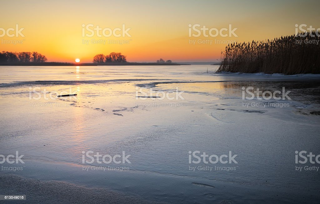 Winter landscape with lake and sunset fiery sky. Composition of stock photo