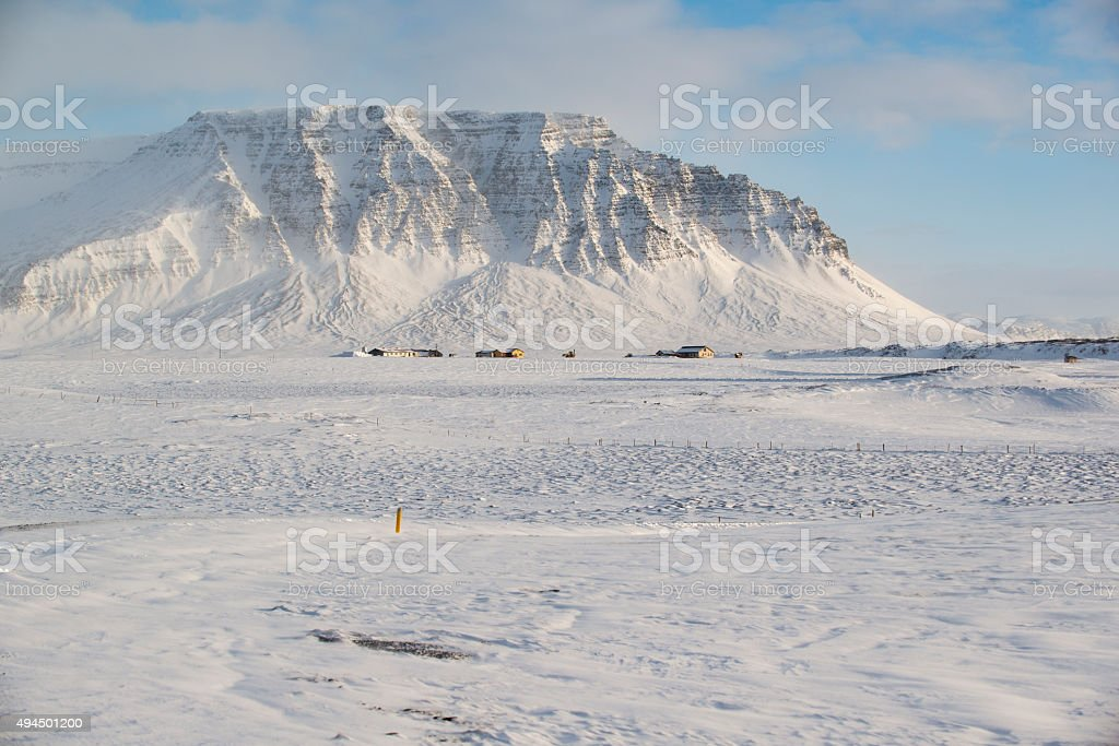 Winter landscape with mountains, snow and small farm houses, Iceland stock photo