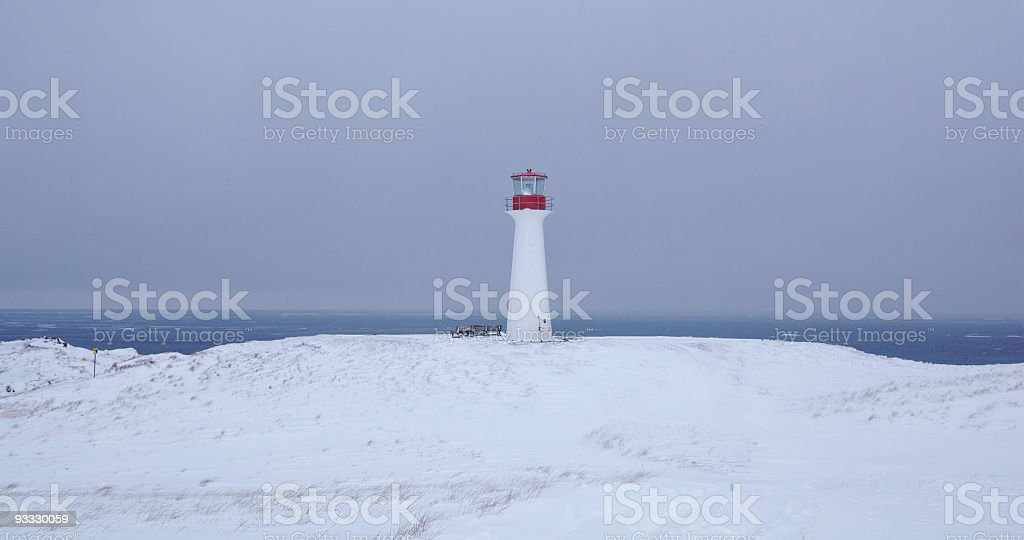 Winter lighthouse with snow and ocean background stock photo