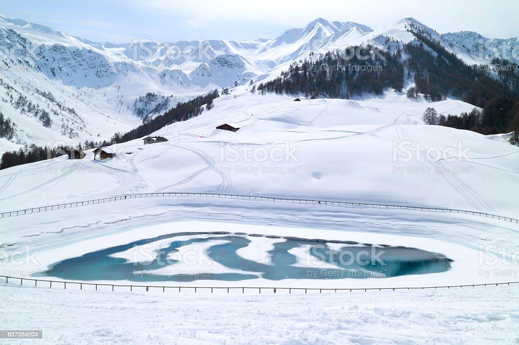 Winter mountains panorama with icy lake, ski slopes stock photo