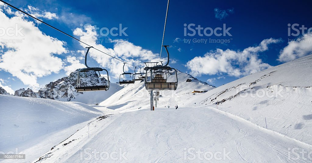 Winter mountains panorama with ski slopes and ski lifts. stock photo