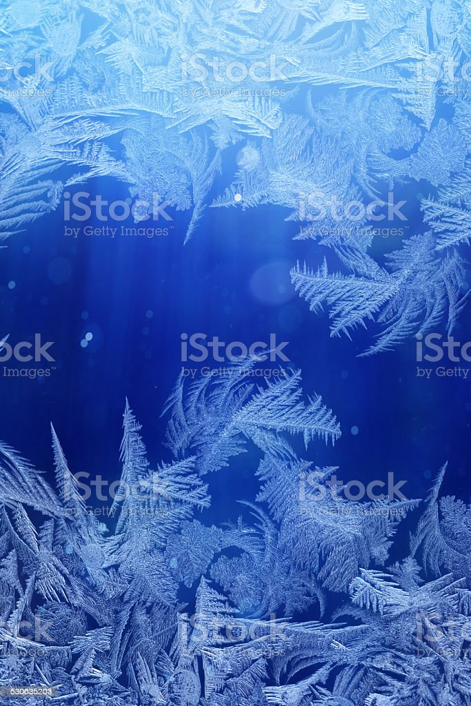Winter night behind frozen window glass stock photo