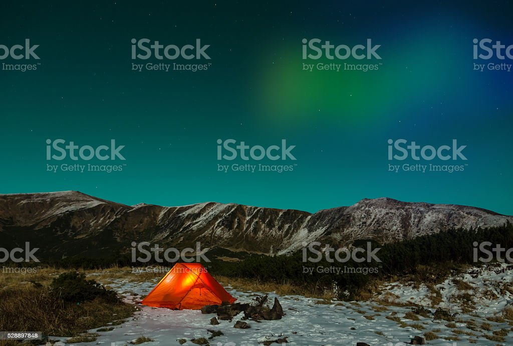 Winter Night landscape with illuminated tent and Polar Lights stock photo