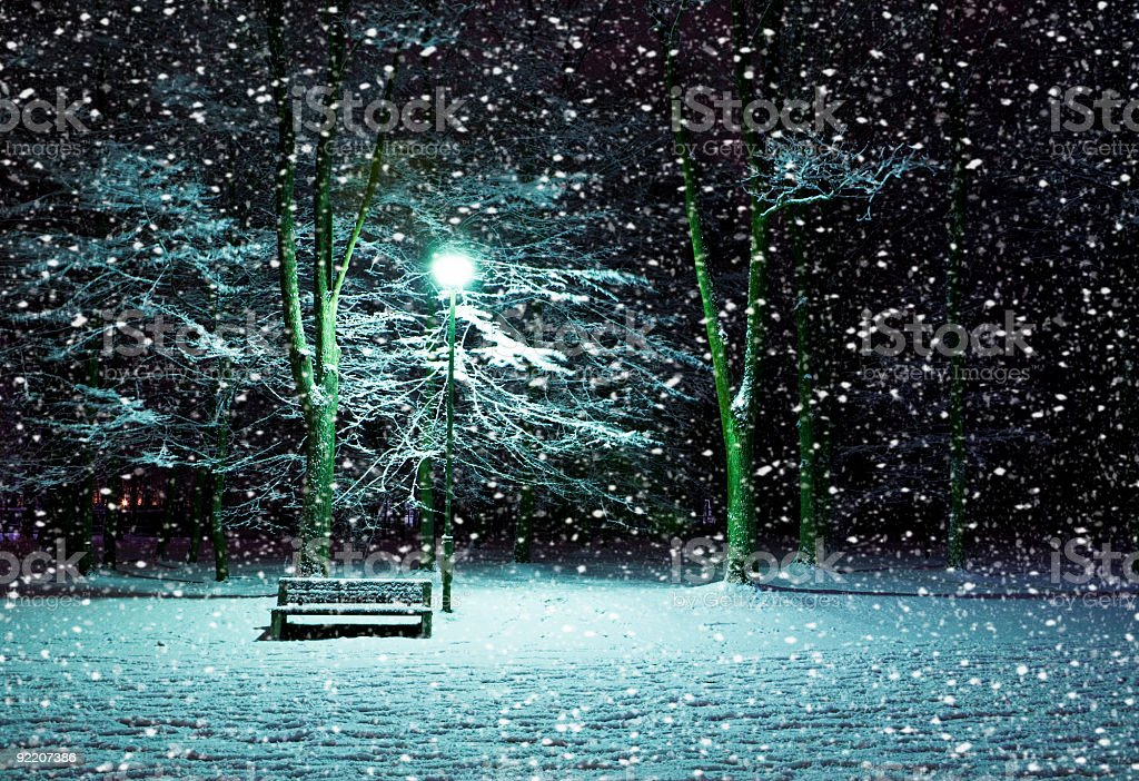 Winter night & snow on a park with just a bench & a light royalty-free stock photo