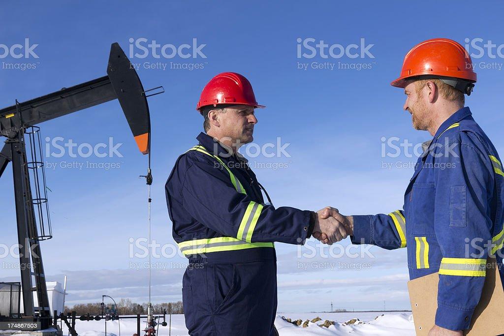 Winter Oil Workers Handshake royalty-free stock photo