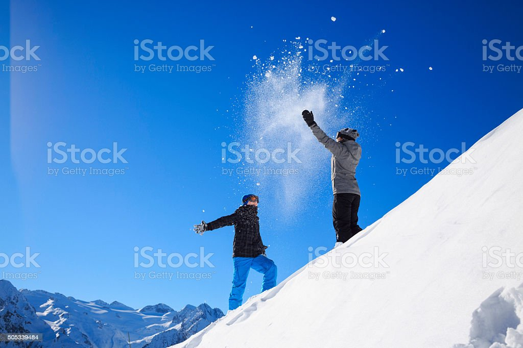 Winter playing   Boy and girl  skiers throwing snow  Snowball fight stock photo