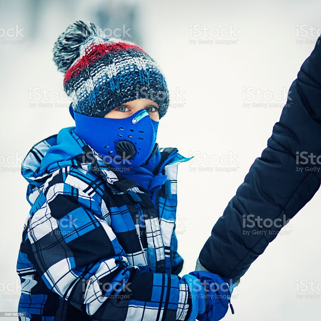 Winter pollution - portrait of boy wearing modern pollution mask stock photo