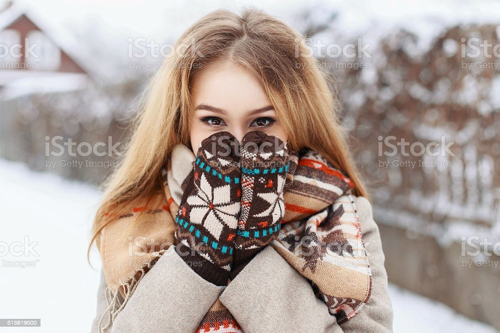 Winter portrait of a girl hiding in her scarf stock photo