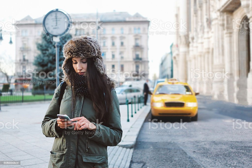Winter portrait of a woman in the city calling taxi stock photo