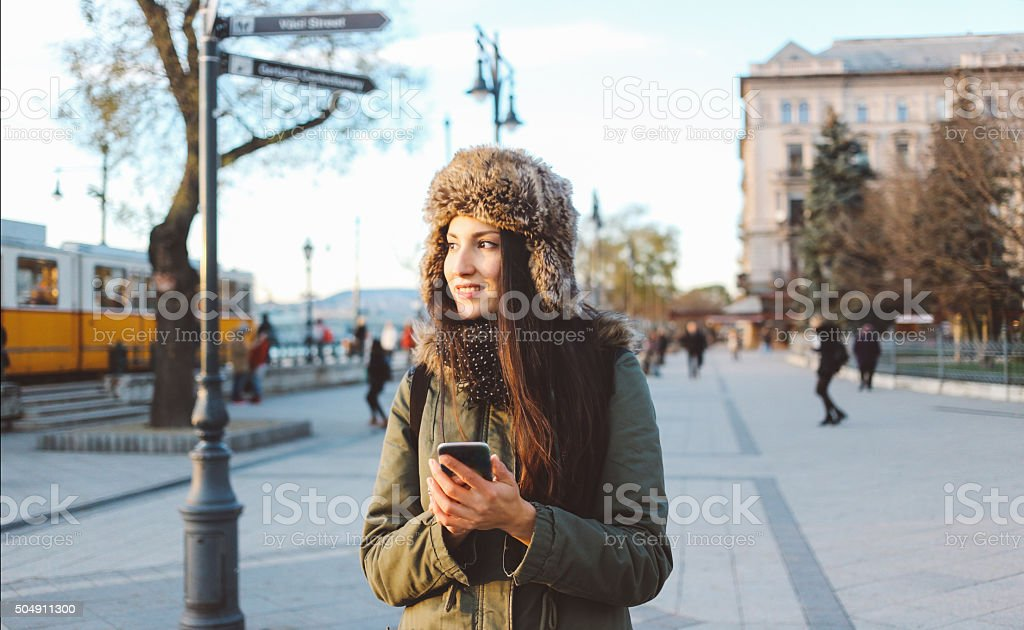 Winter portrait of a woman in the city using smartphone stock photo