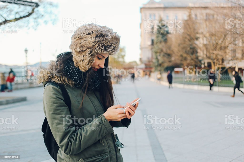 Winter portrait of a young woman in the city texting stock photo