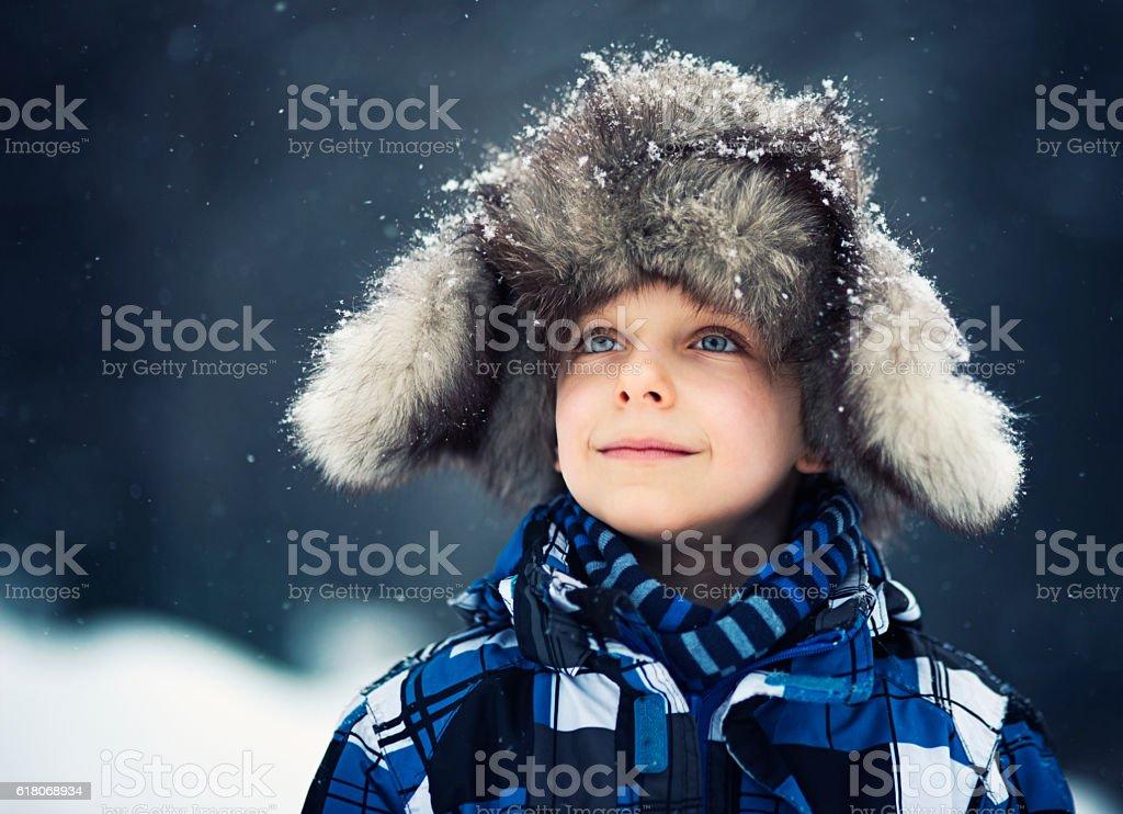 Winter portrait of cute little boy in big fur cap stock photo