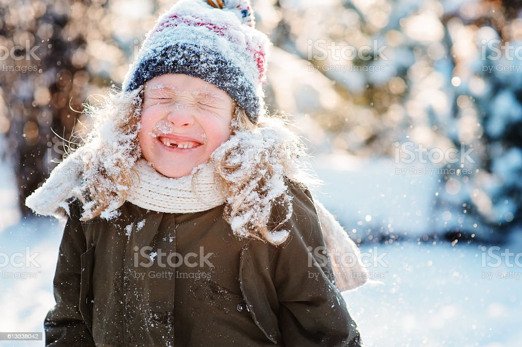 winter portrait of happy kid girl covered with snow stock photo
