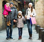 Winter portrait of happy smiling adults with daughters. Focus on