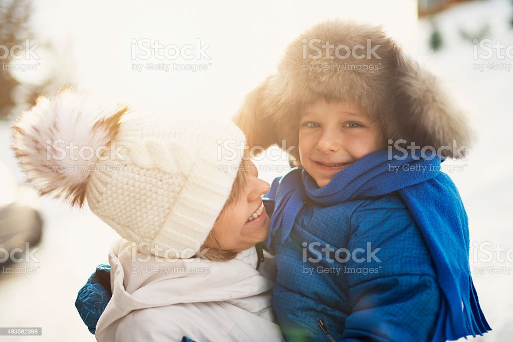 Winter portrait of mother and son on winter walk stock photo