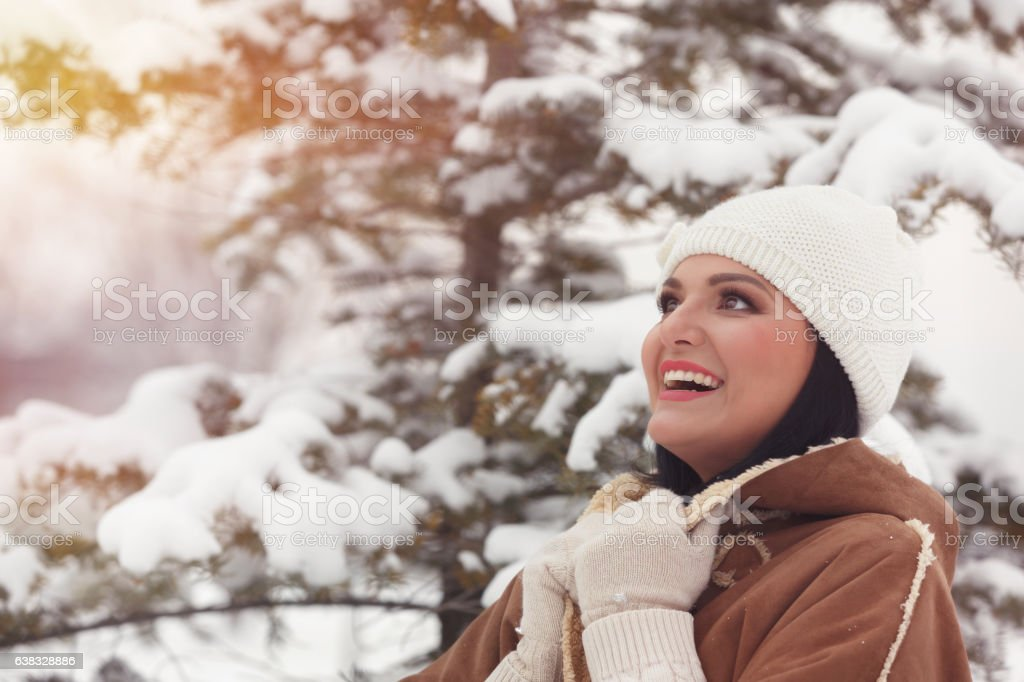 Winter portrait of young beautiful brunette woman in snow park stock photo